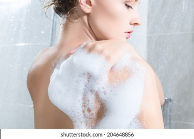 Young woman washing body in a shower. Rear view