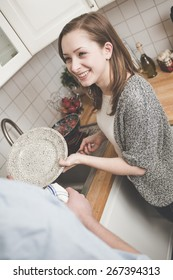 Young woman washing dishes in the kitchen