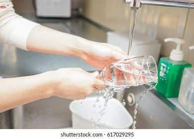 Young woman washing dishes in a kitchen