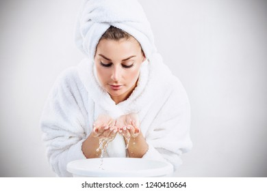Young woman washing face with clean water. Over gray background.
