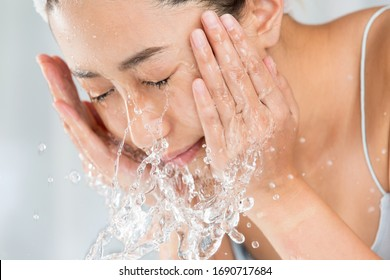 Young woman washing face in room.