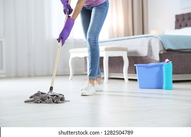 Young woman washing floor with mop in bedroom, closeup. Cleaning service