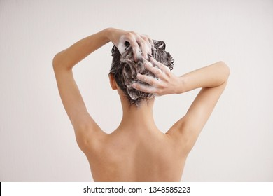 Young woman washing hair on white background