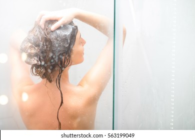 Young woman washing hair with shanpoo in the shower. Back view