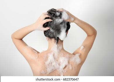 Young woman washing hair while taking shower on white background