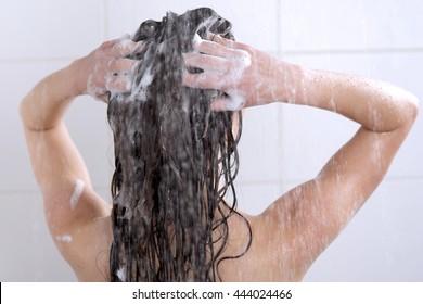 Young woman washing head with shampoo