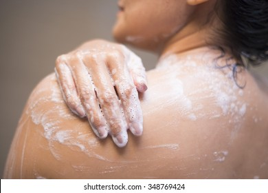 young woman washing her body with shower gel, shower