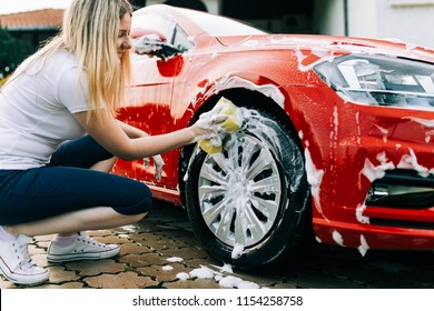 Young woman washing her car with sponge.