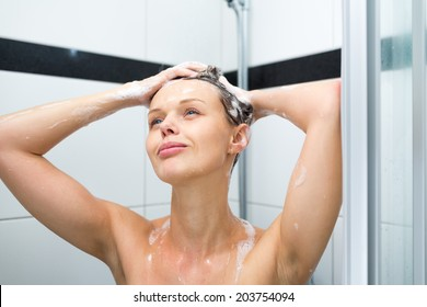 Young woman washing her hair with shampoo, taking a hot long shower