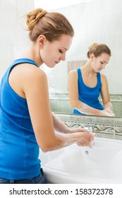 Young woman washing her hands with soap and clean water in bathroom