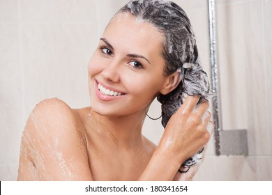 Young woman washing her head in the shower by shampoo