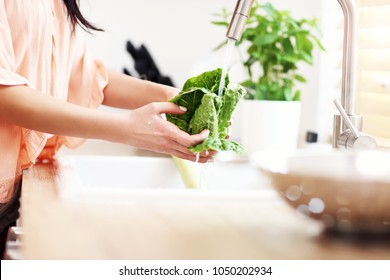 Young woman washing lettuce in modern kitchen