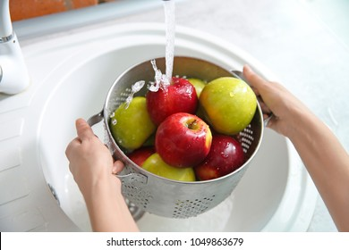 Young woman washing ripe apples in kitchen
