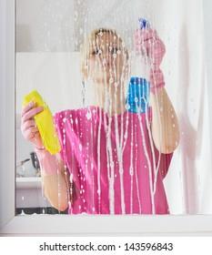Young woman washing the window glass.