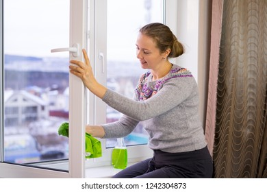 young woman washing windows and laughing merrily