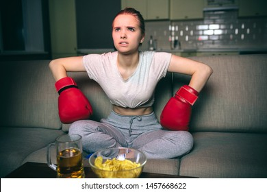Young woman watch boxing on tv at night. Serious upset model sit on sofa and lean forward. Hands in sport gloves. Beer and chips on table. Alone in dark room. Streamming services.