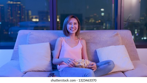 Young woman watch comedy and feel funny at night