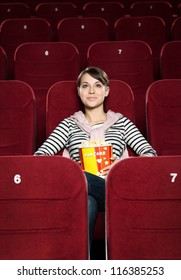 Young woman watching a movie alone at the cinema