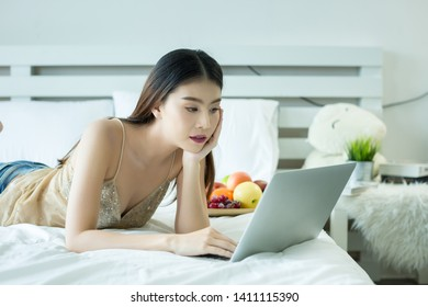 A young woman is watching a movie from a laptop on the bed at home
