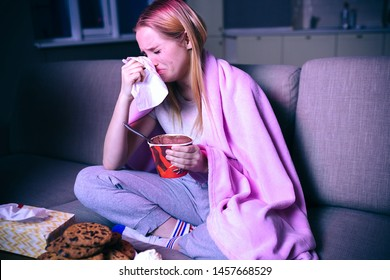 Young woman watching movie at night. Sitting on sofa and crying. Holding tissue close to head. Eating ice cream. Watching sad movie or tv series.