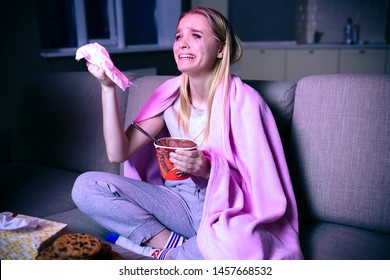 Young woman watching movie at night. Emotional model sitting on sofa and crying. Watching sad movie or tv series. Alone in dark room.