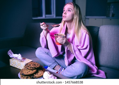 Young woman watching movie at night. Eating ice cream or chocolate with spoon. Cookies on table. Streaming show on tv.