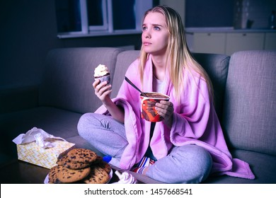 Young woman watching movie at night. Blonde model sitting with hands crossed. Eating pancake and ice cream. Streaming show or tv series.