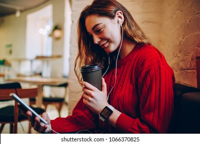 Young woman watching movie online on portable pc and electronic earphones while recreating in coffee shop, hipster girl using wifi in coworking space for making video call on digital tablet
