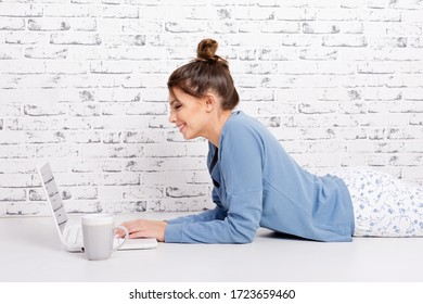 Young woman watching movies or working on laptop at home wearing pajamas