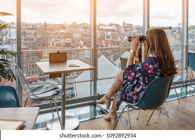 Young woman watching the panorama of the city of Amsterdam, looking through binoculars from the top through the window of the restaurant.
