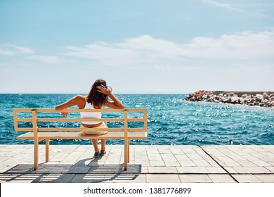 young woman watching the sea sitting on a bench and relax