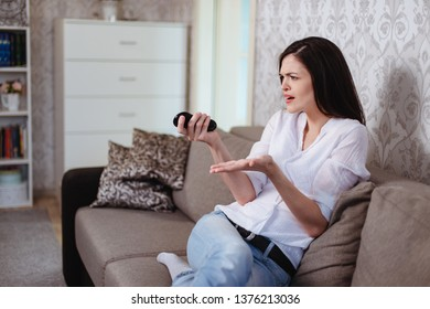 Young woman watching shocking news on TV tonight