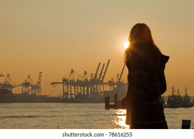 A young woman watching the sun go down over Hamburg
