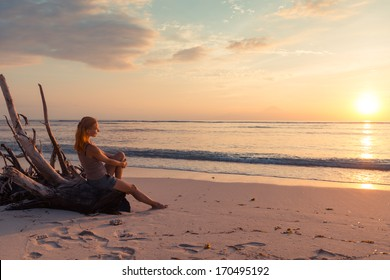 Young woman watching as sun sets over Pacific Ocean
