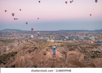 young woman watching sunrise, Goreme Capadocia kapadoya Turkey, Sunrise over the hills with hot air balloons in the sky , colorful landscape