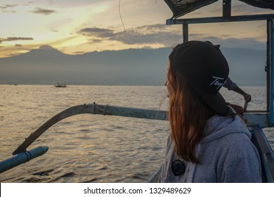 Young woman watching sunrise in traditional balinese fisherman's boats in the ocean, Lovina, north of Bali, Indonesia