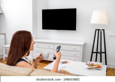 Young woman watching television sitting on the sofa at home. Back view