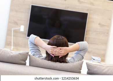 Young woman watching TV in the room