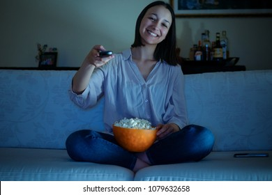 Young woman watching tv sitting on the sofa