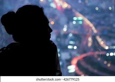 Young woman watching the view from skyscraper. Contours of the woman to background night city. Black woman silhouette in the window of a skyscraper. Dark outline woman watching traffic night city.