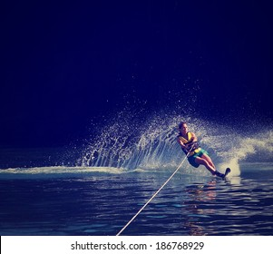 a young woman water skiing on a lake done with a retro vintage instagram filter