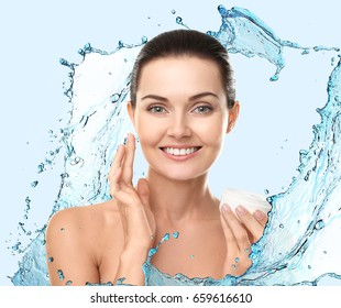Young woman and water splashes on blue background. Beauty concept