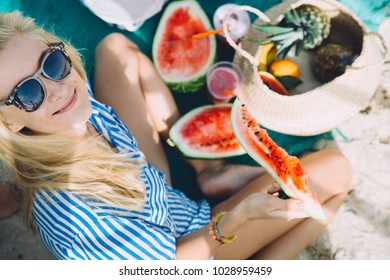 Young woman with a watermelon slice on the beach
