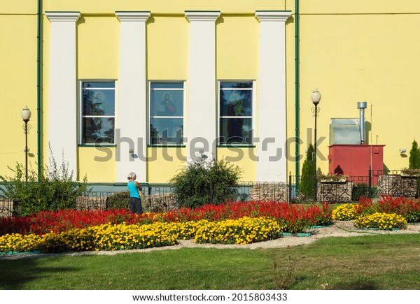 young-woman-waters-flowers-windows-600w-