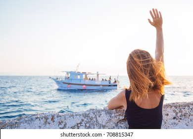 Young woman waving to a boat from the pier