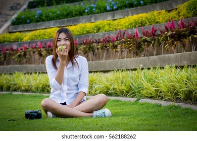 Young woman wear white clothing and holding an apple sitting on the grass.