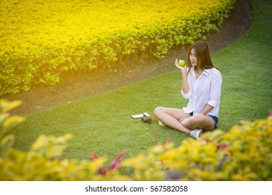 Young woman wear white clothing and holding an apple sitting on the grass. Vintage tone.