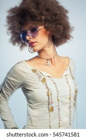 Young woman wearing 1970's style clothing. The model is also wearing sunglasses and various peace-sigh jewelry.