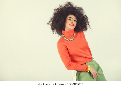 Young woman wearing a 70s retro clothes striking a pose in studio. Disco diva