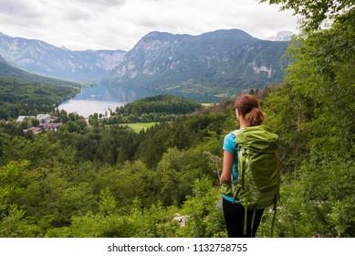 Young woman wearing backpack is admiring panoramic view of lake Bohinj in Bohinj, Slovenia